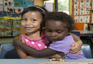 two female children of different ethnicity hugging